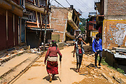 An elderly woman walks down a street flanked by collapsed houses in Chautara, Sindhupalchowk, Nepal on 29 June 2015. Sindhupalchowk was one of the most devastated by the April 25th earthquake and aftershocks that killed over 8000 people and injured over 19000 people, destroying over half a million houses. Photo by Suzanne Lee for SOS Children's Villages