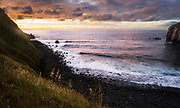 Sunset over Atlantic Ocean at the rocky shore of Sao Miguel, Azores, Portugal.