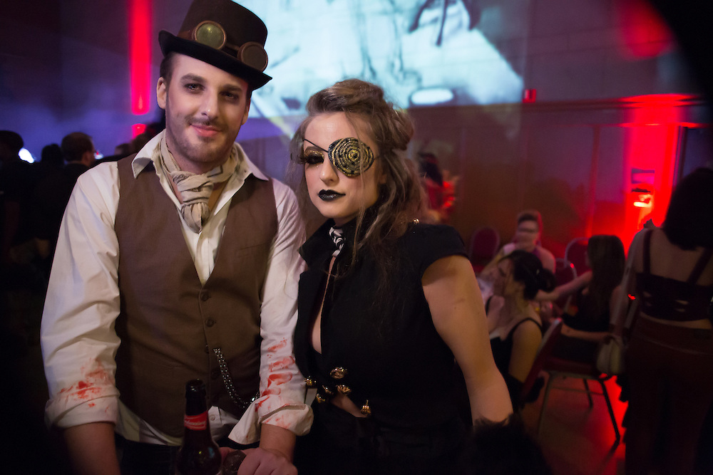 A man with a blood-stained costumed with a woman wearing a jeweled eye patch.