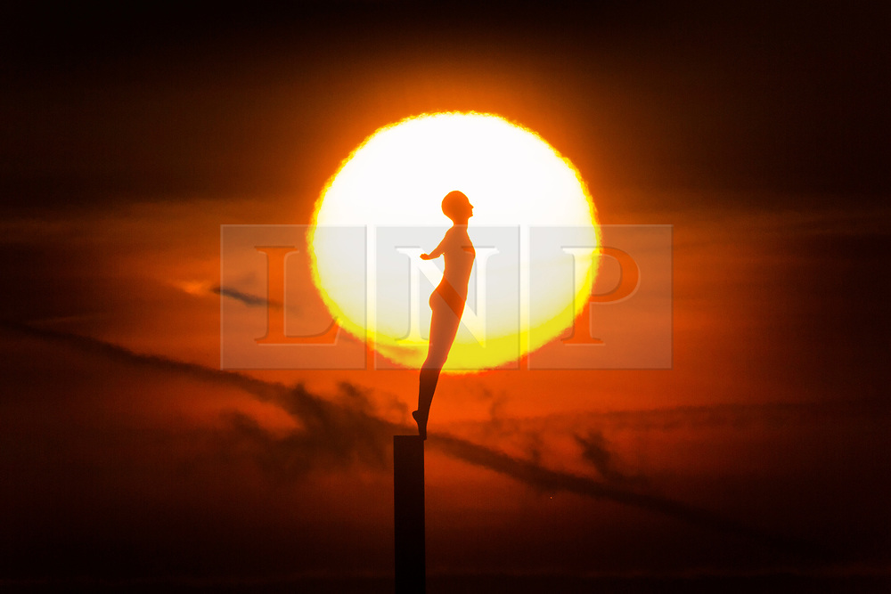 © Licensed to London News Pictures. 12/02/2019. Scarborough UK. The sun rises behind the Diving Bell statue at Scarborough harbour this morning on the Yorkshire coast. Photo credit: Andrew McCaren/LNP
