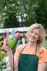 Female shop assistant showing fake bird in greenhouse, Augsburg, Bavaria, Germany