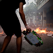 A protester throws cardboard boxes into a burning barricade in Nikis Street near  Syntagma  (Constitution) square, June 29, 2011
