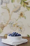 Blueberries in a ramakin, near a window.