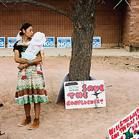 """Tiffany Tracy (left) and Dana Eldridge (right) , who holds Tracy's daughter Yaanivia, stand in protest at a council meeting about the Navajo Generating Station in Window Rock on Monday. Tracy came to the protest to maintain resources for her daughter and students. """"The future generations deserve everything: clean water, air, and a world where their existence isn't exploited for profit."""""""
