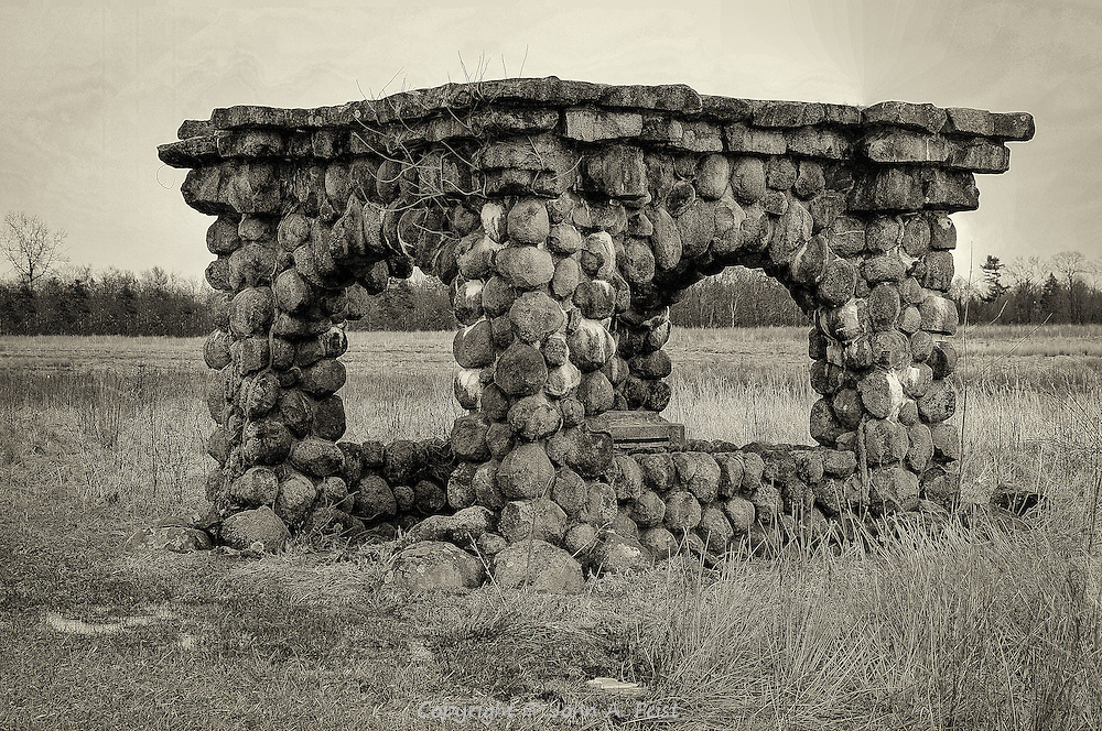 This stone structure is sitting in the middle of a very large and otherwise empty field.  It was built of stone to copy a bygone era.