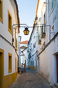 Women hanging washing in street of white and yellow houses and cobble stones and lanterns in Evora, Portugal