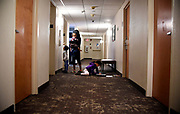 A Puerto Rican girl colors on the floor in the hallway of the Red Roof Inn, Friday, Jan. 26, 2018, in Hartford, Conn.  Families from Puerto Rico having been staying at the hotel since being displaced by Hurricane Maria in November. (Jessica Hill for the New York Times)