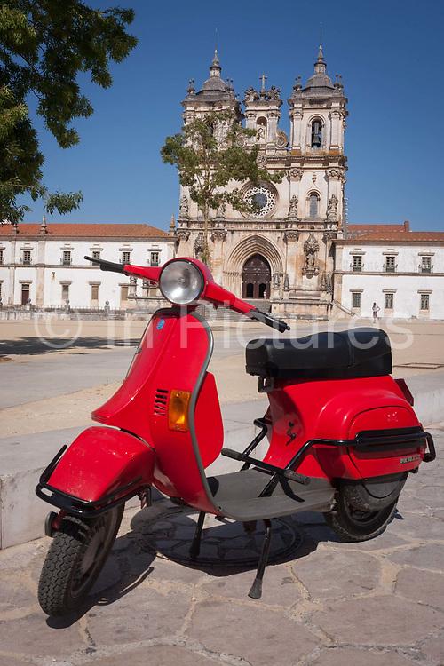 A shiny red Vespa scooter parked opposite Alcobaca Monastery Mosteiro de Santa Maria de Alcobaca, on 16th July, at Alcobaca, Portugal.