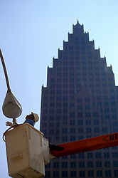 Stock photo of a man in a cherry picker working on a street lamp in downtown Houston Texas
