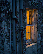Light shines from a window in a house near the harbour in Ullapool before dawn breaks.