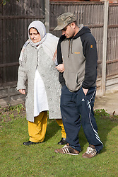 South Asian woman walking a in garden with her son.