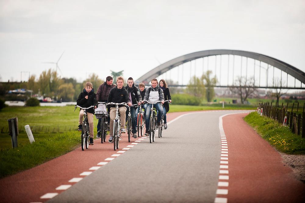 Nederland, Culemborg, 19 april 2012.Schoolkinderen fietsen van school naar huis over de dijk langs de lek...Foto(c): Michiel Wijnbergh