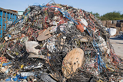 Pile of mixed plastic copper cable of various sorts; domestic and commercial waiting to be sorted at metal recycling centre,