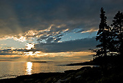 SUBJECT: Sunset at Newagen, Maine. IMAGE: The sunset sends sunbursts into the clouds and water off Southport Island
