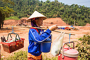 13 MARCH 2013 - ALONG HIGHWAY 13, LAOS: A Lao woman walks past a construction near the end of Highway 13 in the Boten Special Economic Zone. The site will eventually become truck and car parking for people shopping in the Chinese markets in the SEZ. The SEZ is in Laos immediately south of the Lao Chinese border. It has turned into a Chinese enclave but many of the businesses struggle because their goods are too expensive for local Lao to purchase. Some of the hotels and casinos in the area have been forced to close by the Chinese government after reports of rigged games. The paving of Highway 13 from Vientiane to near the Chinese border has changed the way of life in rural Laos. Villagers near Luang Prabang used to have to take unreliable boats that took three hours round trip to get from the homes to the tourist center of Luang Prabang, now they take a 40 minute round trip bus ride. North of Luang Prabang, paving the highway has been an opportunity for China to use Laos as a transshipping point. Chinese merchandise now goes through Laos to Thailand where it's put on Thai trains and taken to the deep water port east of Bangkok. The Chinese have also expanded their economic empire into Laos. Chinese hotels and businesses are common in northern Laos and in some cities, like Oudomxay, are now up to 40% percent. As the roads are paved, more people move away from their traditional homes in the mountains of Laos and crowd the side of the road living off tourists' and truck drivers.    PHOTO BY JACK KURTZ