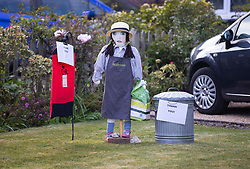 © Licensed to London News Pictures. 27/04/2020. Capel, UK. A scarecrow depiction of a Waitrose worker stands in tribute along with a post box and dustbin at the front garden of a house in the Surrey village of Capel. Residents of the village have resurrected their summer tradition of scarecrows in tribute to NHS medical staff and other key workers. Up to 30 of the life size home made doll like characters can be seen in front gardens throughout the village. The public have been told they can only leave their homes when absolutely essential, in an attempt to fight the spread of coronavirus COVID-19 disease. Photo credit: Peter Macdiarmid/LNP