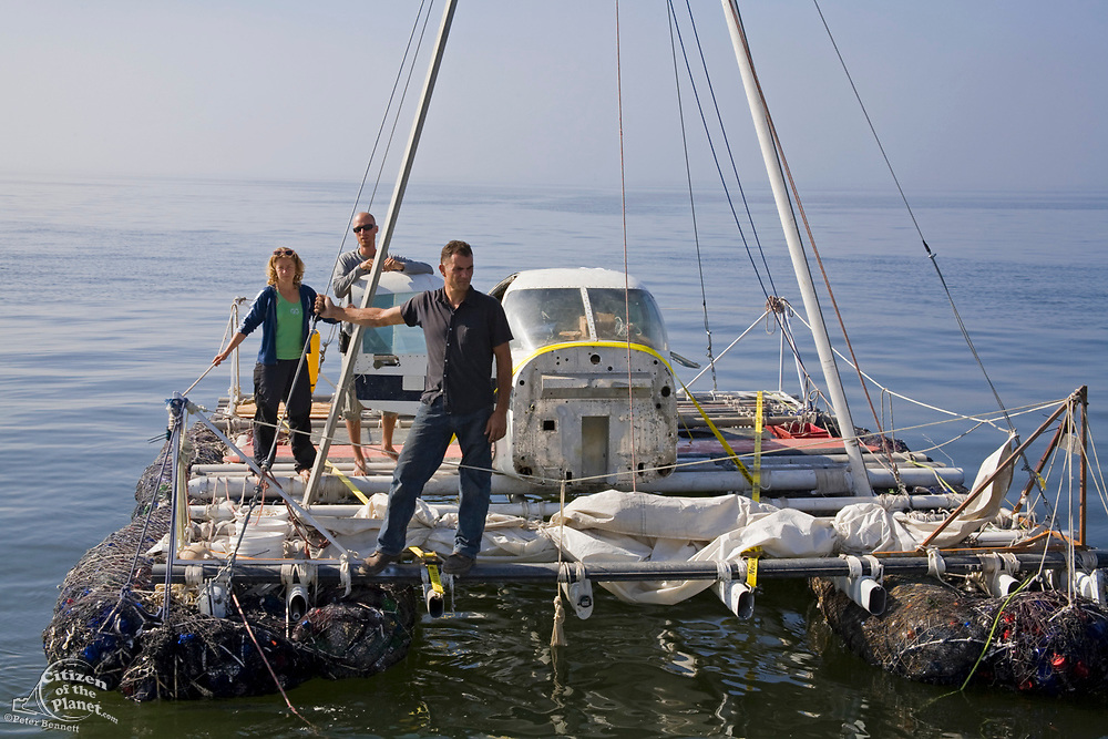"""(l to R) Anna Cummin, Joel Paschal and Marcus Eriksen on the maiden voyage of the """"Junk"""" raft, out of Long Beach Harbor. 5/18/08.  in June of 2008, the raft named """"Junk""""  will sail 2,100 miles from Los Angeles to Hawaii to bring attention to the plastic marine debris (nicknamed the plastic soup) accumulating in the North Pacific Gyre. Designed by Dr. Marcus Eriksen and Joel Paschal, the raft is constructed from 20,000 plastic bottles, an airplane fuselage, discarded fishing nets, a solar generator, and a bicycle generator. California, USA"""