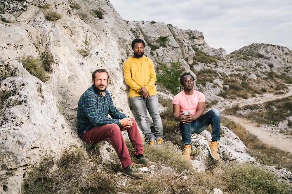 """MATERA, ITALY -6 OCTOBER 2019: (L-R) Vito Castoro (37, farmer), Yussif Bamba (founder of the NGO AIIMS) and Papa Latyr Faye (aka Hervé, President of the NGO """"Ghetto Out Casa Sankara""""), respectively performing the roles of Jesus Christ's Apostles Bartholomew, Matthew and Peter, pose for a portrait during the production of """"The New Gospel"""", a film by Swiss theatre director Milo Rau, in Matera, Italy, on October 6th 2019.<br /> <br /> Theatre Director Milo Rau filmed the Passion of the Christ  under the title """"The New Gospel"""" with a cast of refugees, activists and former actors from Pasolini and Mel Gibson's films.<br /> <br /> The role of Jesus is performed by Yvan Sagnet, a Political activist born in Cameroon and who worked on a tomato farm when in 2011 he revolted against the system of exploitation and led the first farm workers' strike in southern Italy. In a series of public shoots in the European Capital of Culture Matera, Jesus will proclaimed the Word of God, was crucified (October 6th 2019) and finally rose from the dead in Rome, the capital of Catholic Christianity and seat of one of the most xenophobic governments in Europe (October 10th 2019).<br />  <br /> Parallel to the film, the humanistic message of the New Testament was transformed into the present: at the beginning of September, the campaign """"Rivolta della Dignità"""" (Revolt of Dignity), which demanded fair working and living conditions     for refugees, global freedom of travel and civil rights for all, started with a march from the southern Italian refugee camps. """"It's about putting Jesus on his feet,"""" director Milo Rau said. Led by Jesus actor Yvan Sagnet, the campaign fights for the rights of migrants who came to Europe via the Mediterranean to be enslaved by the Mafia in the tomato fields of southern Italy and to live in ghettos under inhumane conditions. The campaign and the film thus create a """"New Gospel"""" for the 21st century, a manifesto of solidarity with the poorest, a revolt for a more just """