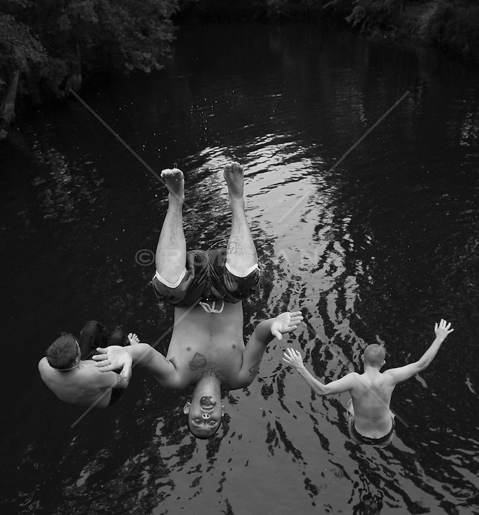 Three young men diving into a river in South Carolina