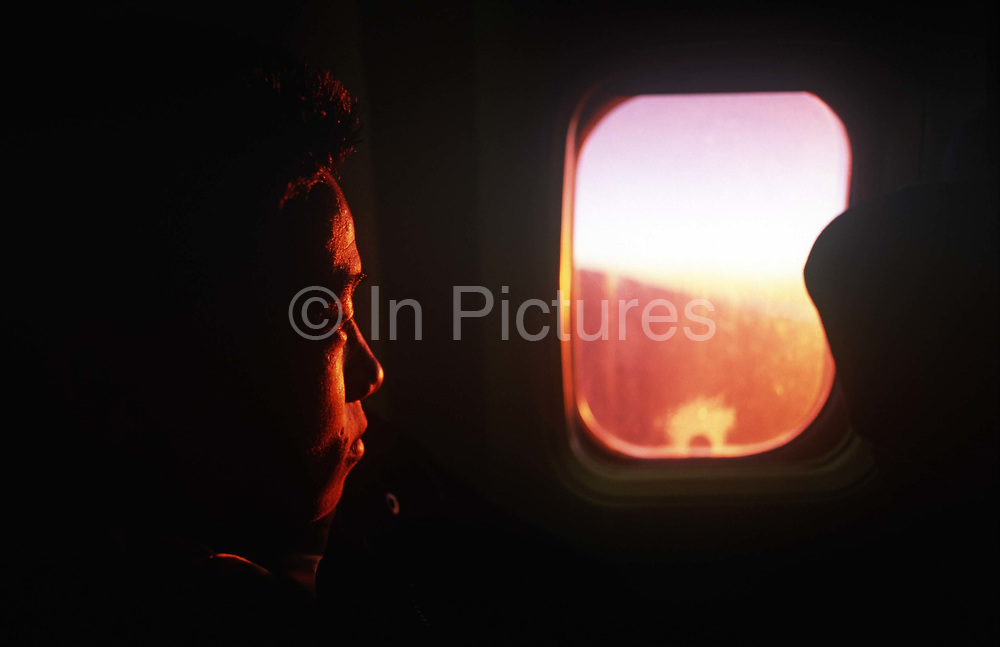 A newly-recruited Nepali boy stares through the window of a Nepal Airlines airliner during his flight from his Himalayan homeland to the UK where his 2-year training for the British Army will begin, on 16th January 1997, in Kathmandu, Nepal. He is leaving behind his family for England where the British army is to make him a fully-trained soldier in the Gurkha Regiment. Some 60,000 young Nepalese boys aged between 17 - 22 or 25 for those educated enough to become clerks or communications specialists report to designated recruiting stations in the hills each November, most living from altitudes ranging from 4,000 - 12,000 feet. After initial selection, 7,000 are accepted for further tests from which 700 are sent down here to Pokhara in the shadow of the Himalayas. Only 160 of the best boys succeed in the flight to the UK. The Gurkhas training wing in Nepal has been supplying youth for the British army since the Indian Mutiny of 1857.