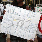 """People hold signs in Lake Eola park during the """"National Moment of Silence"""" event at the Lake Eola bandshell in downtown Orlando, Florida on Thursday, August 14, 2014. In light of the recent killing of eighteen year old Mike Brown in Ferguson, Missouri, citizens across America are gathering in solidarity to hold vigils and observe a moment of silence to honor victims of suspected police brutality. (AP Photo/Alex Menendez)"""