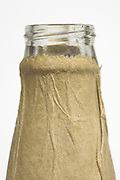 close up of a beer bottle neck wrapped in a brown paper bag