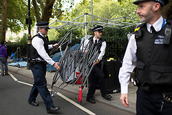 © Licensed to London News Pictures. 07/10/2019. London, UK. Police officers remove a gazebo from an an Extinction Rebellion Roadblock on Millbank . Photo credit: George Cracknell Wright/LNP
