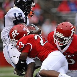 Sep 12, 2009; Piscataway, NJ, USA; Howard wide receiver Willie Carter (12) is tackled by Rutgers cornerback Brandon Bing (23) and Rutgers cornerback Zaire Kitchen (29) during the first half of Rutgers' 45-7 victory over Howard in NCAA College Football at Rutgers Stadium.