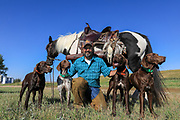 John Zeman with his German Shorthairs (left-to-right) Willy, Liza, Louie, and Luna. Buckwheat the horse stands behind with a game strap carrying sharptails and hungarian partridge.