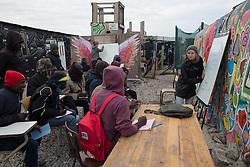 """Calais, Pas-de-Calais, France - 16.10.2016    <br />     <br /> Volunteers give language courses in a school in the camp. """"Jungle"""" refugee camp on the outskirts of the French city of Calais. Many thousands of migrants and refugees are waiting in some cases for years in the port city in the hope of being able to cross the English Channel to Britain. French authorities announced that they will shortly evict the camp where currently up to up to 10,000 people live.<br /> <br /> Freiwillige geben Sprachkurse in einer Schule im Camp. """"Jungle"""" Fluechtlingscamp am Rande der franzoesischen Stadt Calais. Viele tausend Migranten und Fluechtlinge harren teilweise seit Jahren in der Hafenstadt aus in der Hoffnung den Aermelkanal nach Großbritannien ueberqueren zu koennen. Die franzoesischen Behoerden kuendigten an, dass sie das Camp, indem derzeit bis zu bis zu 10.000 Menschen leben Kürze raeumen werden. <br /> <br /> Photo: Bjoern Kietzmann"""