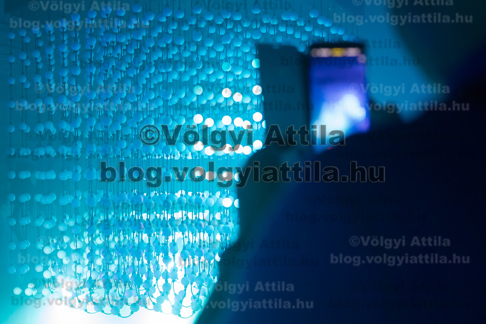 Visitors photographs with her mobile phone an artistic light installation during the Zsolnay Light Festival held in central Pecs, Hungary on June 30, 2018. ATTILA VOLGYI