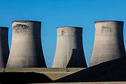 A huge pile of black coal next to the cooling towers of Ratcliffe-on-Soar coal fired power station, owned and operated by Uniper at Ratcliffe-on-Soar on the 26th of February 2021 in Nottinghamshire, United Kingdom. The plant emits 8–10 million tonnes of CO2 annually. It has a generating capacity of 2,116 MW,  enough electricity to meet the needs of approximately 2 million homes.