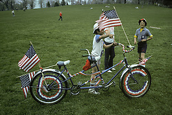Patriotic youngsters with flag decorated bicycle built for two. Stock photo