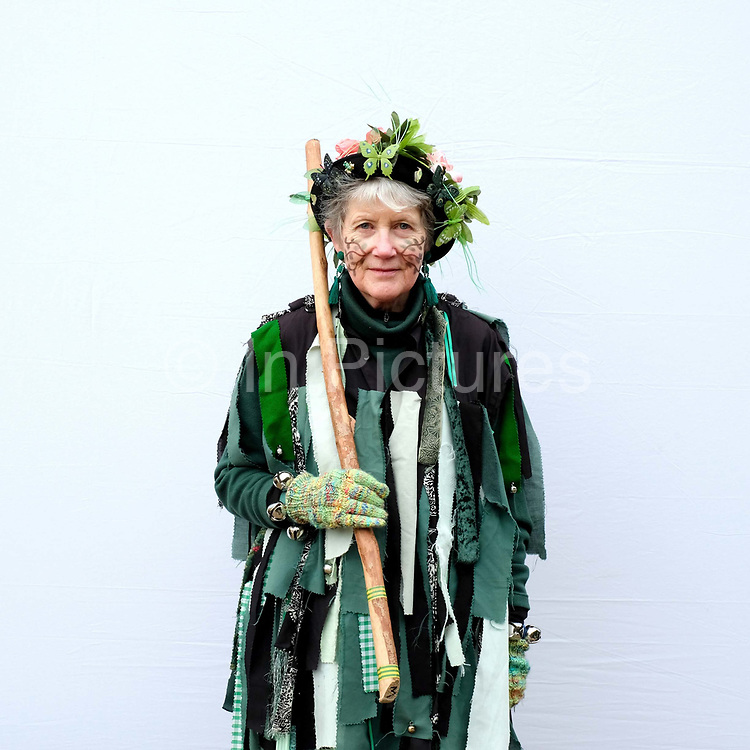 Portrait of a Makara Morris dancer wearing traditional costume at an orchard-visiting wassail at Sledmere House in the Yorkshire Wolds, United Kingdom on 20th January 2018. Wassail is a traditional Pagan winter celebration in cider-producing regions of England, reciting incantations and singing to the trees to promote a good harvest for the coming year. Pieces of toast soaked in cider are hung in the branches to attract robins to the tree as these are said to be the good spirits of the orchard. To ward off evil spirits, villagers scare them away by banging pots and pans and making as much noise as possible