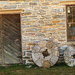 Old mill stones leaning against a stone wall building in Lancaster County, PA.
