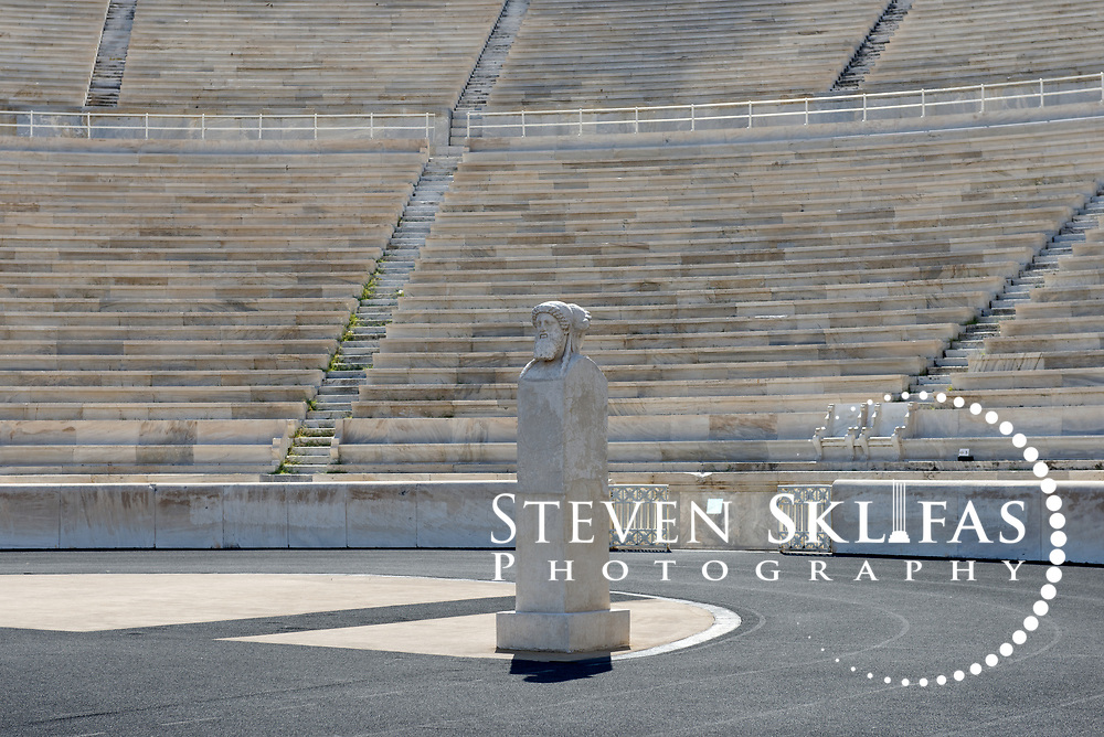 Athens. Greece. View of one of the two side distinctive herms (ancient stone carved head or bust) located at the curved end of the stadium. The stone sculpture depicts two male figures, one young male figure is facing towards the grandstand, and the other an older beared male figure is facing the track. The Panathenaic (Kallimarmaro) stadium was used for the first international Olympic games of the modern era in 1896.  The completely marble stadium occupies the exact site of the original, built in 330BC which was used for the ancient Panathenaic games (part of the larger religious festival, the Panathenaia).