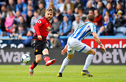 Manchester United's Luke Shaw (left) and Huddersfield Town's Erik Durm battle for the ball during the Premier League match at the John Smith's Stadium, Huddersfield.