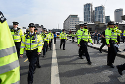 "© Licensed to London News Pictures. 18/04/2019. LONDON, UK.  Police arrive to request protesters on Waterloo Bridge to move on from ""London: International Rebellion"", on day four of a protest organised by Extinction Rebellion. Protesters are demanding that governments take action against climate change.  Marble Arch, Oxford Circus, Piccadilly Circus, Waterloo Bridge and Parliament Square have been blocked by activists in the last three days.  Police have issued a section 14 order requiring protesters to convene at Marble Arch only so that the protest can continue.  Photo credit: Stephen Chung/LNP"