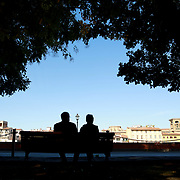 FLORENCE, ITALY - NOVEMBER 01: A couple relax in a park beside the River Arno running through the city of Florence, Italy. 1st November 2017. Photo by Tim Clayton/Corbis via Getty Images)