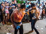 04 NOVEMBER 2014 - YANGON, MYANMAR: Burmese men flagellate themselves with chains and razors in front of Mogul Mosque (Masjid) on Ashura in Yangon. The flagellation shows solidarity with Hussein and his family. Mogul Mosque is the principal Shia mosque in Yangon. Ashura commemorates the death of Hussein ibn Ali, the grandson of the Prophet Muhammed, in the 7th century. Hussein ibn Ali is considered by Shia Muslims to be the third imam and the rightful successor of Muhammed. He was killed at the Battle of Karbala in 610 CE on the 10th day of Muharram, the first month of the Islamic calendar. According to Myanmar government statistics, only about 4% of the population is Muslim. Many Muslims have fled Myanmar in recent years because of violence directed against Burmese Muslims by Buddhist nationalists.    PHOTO BY JACK KURTZ