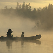 A canoeist with his dog paddling across a small northern lake during a foggy early morning in northern MInnesota.