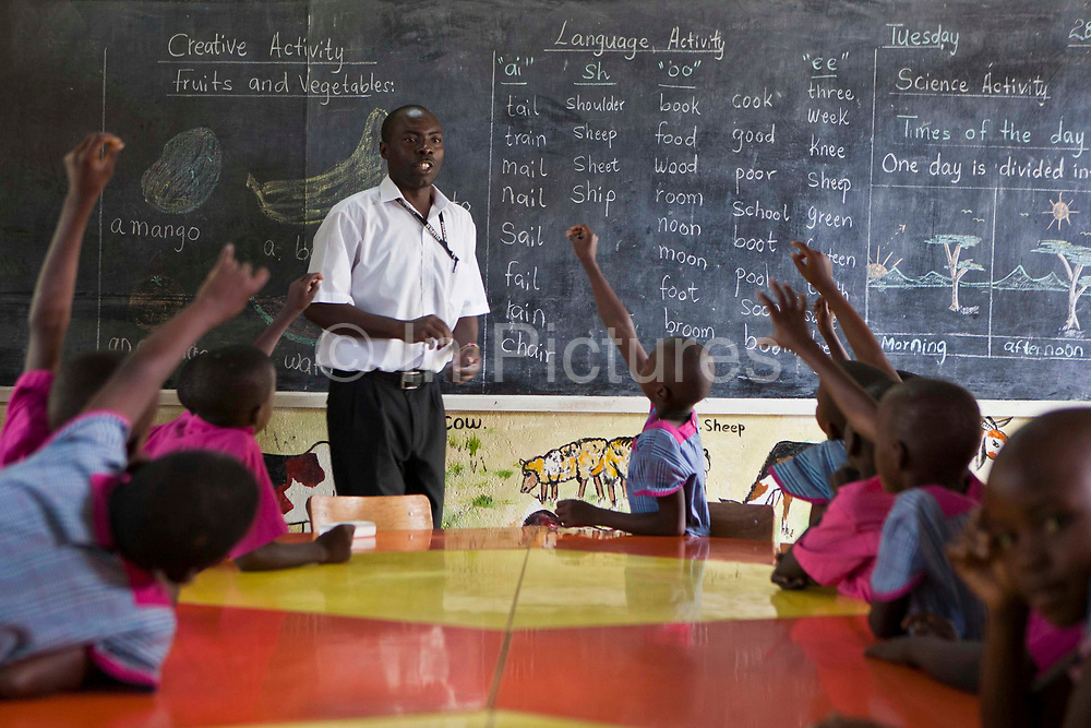 Luthur teaches children in K3, (5 – 6 years old) that attend the kindergarten school learn to read and write English during lessons at the Wema Centre, Mombassa, Kenya. Wema is a NGO organisation in Kenya that provides rehabilitation programs for street children; poor, disadvantaged youth; and, orphaned and vulnerable children affected by poverty. Emotional support and education enables the children reintegration back into society.