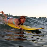 Central America, Costa Rica, Tamarindo. Female surfer paddles into wave in Costa Rica.