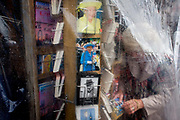 Queen Elizabeth and Winston Churchill appear on a rack of postcards in Westminster, central London. A woman sorts through the tourist souvenirs, just visible after recent rain which has made the capital wet and so tourist trinkets and souvenirs have been covered with clear sheeting. We see the monarch the Queen and her former Prime Minister from Britain's wartime era, peering from behind the covering,