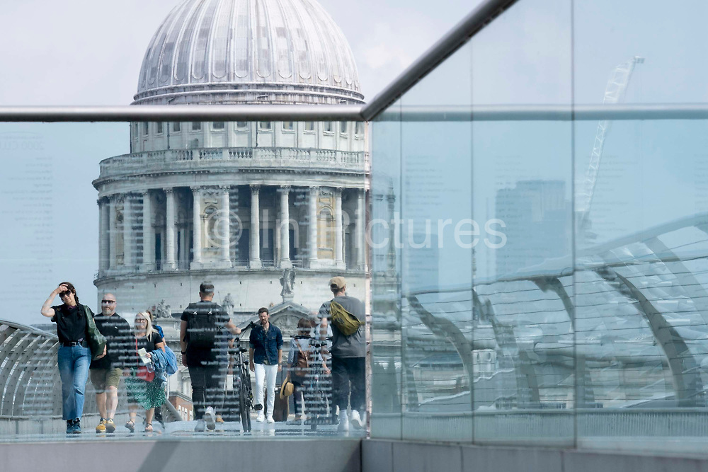 With the dome of St Pauls cathedral in the distance, pedestrians cross the river Thames on the Millennium Bridge, on 24th June 2021, in London, England. Londons newest river crossing for 100-plus years coincided with the Millennium. It was hurriedly finished and opened to the public on 10 June 2000 when an estimated 100,000 people crossed it to discover the structure oscillated so much that it was forced to close 2 days later. Over the next 18 months designers added dampeners to stop its wobble but it already symbolised what was embarrassing and failing in British pride. Now the British Standard code of bridge loading has been updated to cover the swaying phenomenon, referred to as Synchronous Lateral Excitation.