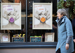 © Licensed to London News Pictures. 04/03/2019. Salisbury, UK. Prime Minister Theresa May emerges from a hairdressers past posters that say 'Being normal is boring' during a visit to Salisbury on the first anniversary of the poisoning of former Russian spy Sergei Skripal and his daughter Yulia in March 2018. They both survived the nerve agent attack but a resident of nearby Amesbury, Dawn Sturgess, died in June 2018 after coming in contact with the poison. Two Russians have been named in connection with the attack. Photo credit: Peter Macdiarmid/LNP