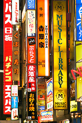 Many bright advertising signs at night in Shinjuku Tokyo