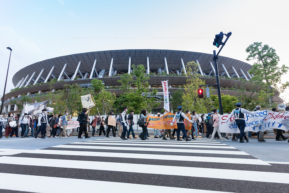 People take part in a demonstration against the delayed 2020 Tokyo Olympics Games in Gaiemmae, Tokyo, Japan. Sunday May 9th 2021. About 100 people took part in a demo outside the Japanese Olympic Committee museum and marched around the new Olympic Stadium to protest holding the event while the  the COVID-19 pandemic is still seriously affecting Japan.