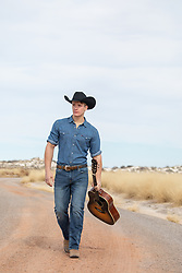 cowboy walking on a dirt road with a guitar
