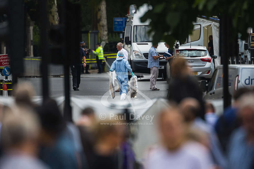 Forensics officers examine the car and surrounding scene outside Parliament after the driver of a silver Ford Fiesta appeared to deliberately run down pedestrians and cyclists, leaving two needing hospitalisation in what is thought to be a terrorism incident. London, August 14 2018.
